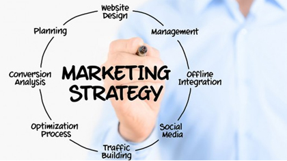 Man holding a pen with the words 'marketing strategy' inside a circle and related words around it.